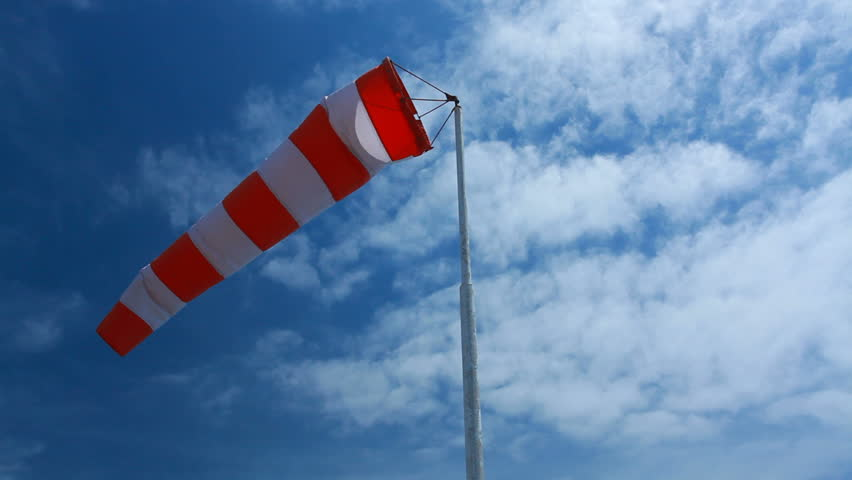 wind sock - red and white pointer indicating strength and direction of the wind against the blue sky with fluffy clouds