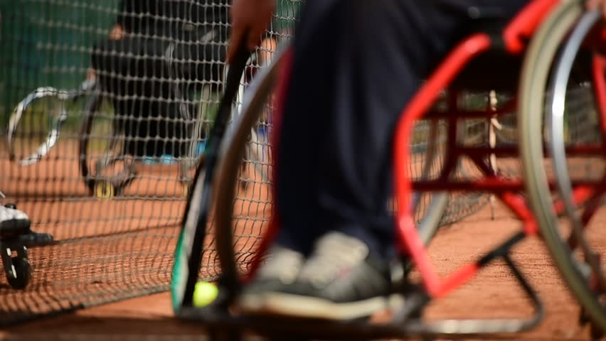 Wheelchair tennis player is seen behind the tennis net on a clay court | Shutterstock HD Video #12154481