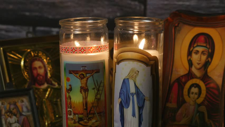 Religious candles burning with icones of jesus and mother Mary in the background. Filmed in 4K.