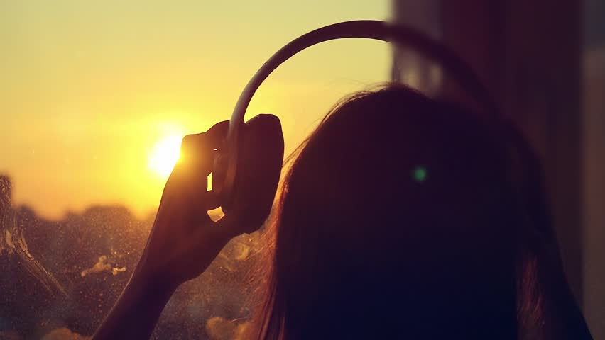 Attractive young woman wears headphones listening to music on the music player at blurred city background. enjoying the tunes in slowmotion at sunset. 1920x1080