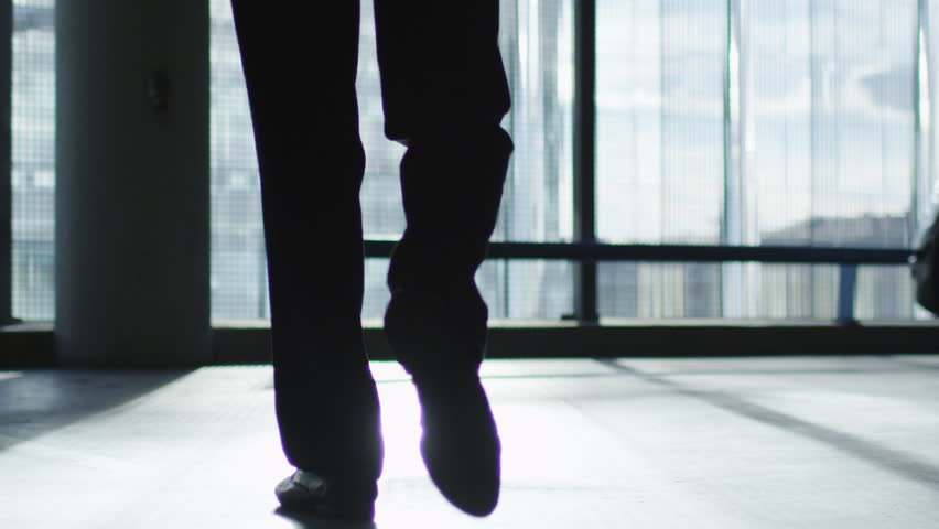 Businessman in a suit is walking towards a big window that looks at the buildings that reflect sunlight. Shot on RED Cinema Camera in 4K (UHD).
