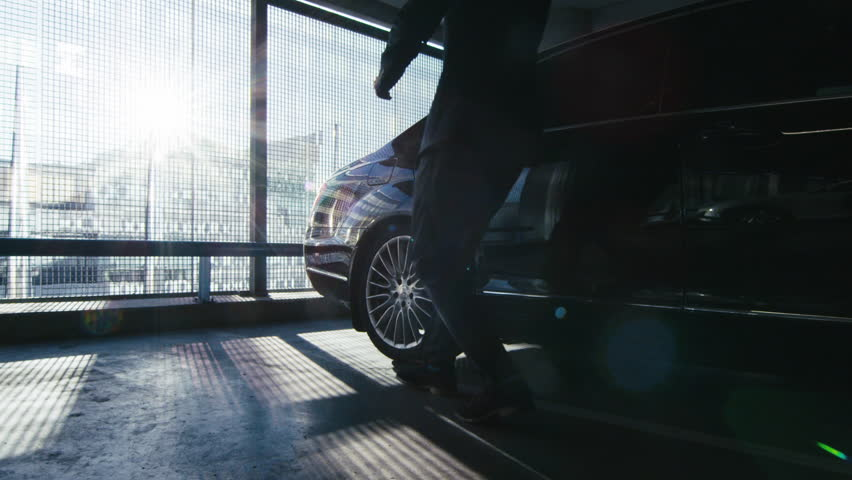 Driver opens the door for a businessman who speaks on the phone to step out of the black executive car at a garage parking. Shot on RED Cinema Camera in 4K (UHD).