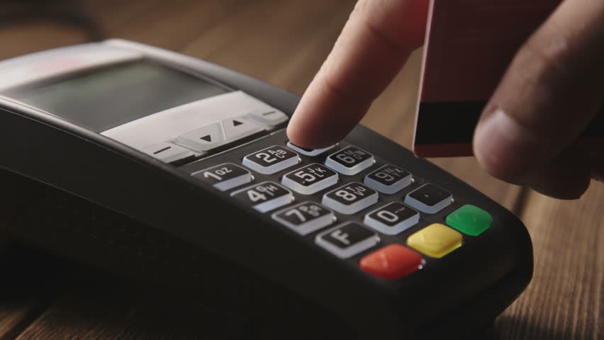 Man's hand pushing the button and swipe credit card payment on pos terminal standing on wooden desk. - HD stock video clip