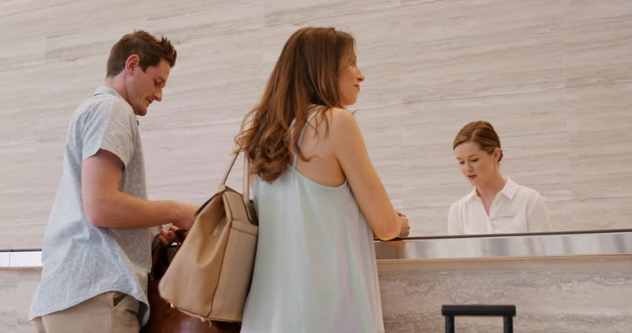 Attractive happy couple arriving at hotel reception lobby travelling on vacation checking in carrying luggage on honeymoon using payment device