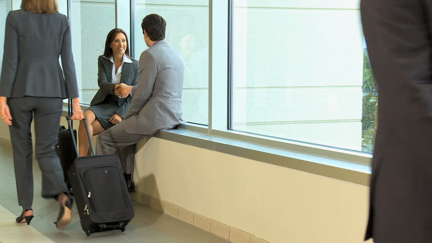 multi ethnic male female business businessman businesswoman airport atrium travel luggage ambitious successful wireless smart phone