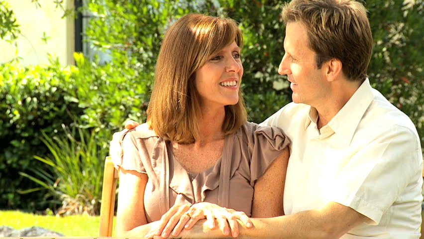 Caucasian American couple male female attractive together outdoor home garden happy relaxation lifestyle medical insurance protection - HD stock video clip