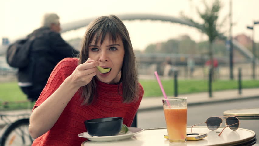 Attractive woman eating tasty soup in cafe in the city