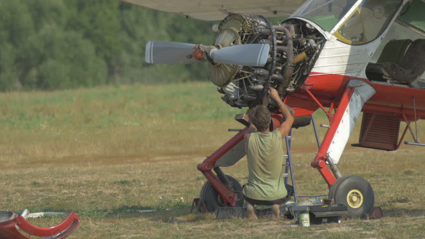 The engineer repairing the engine of the plane on the glade