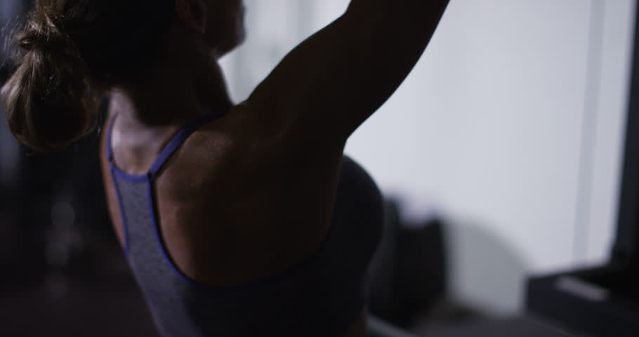 An attractive woman training with weight-lifting training machine at her local gym in slow motion. Shot on RED Epic.