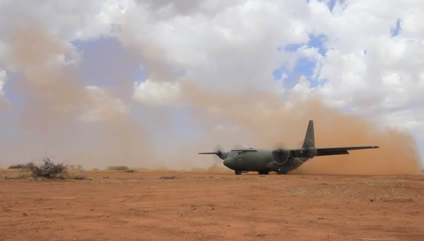 NANYUKI, KENYA - CIRCA OCTOBER 2015 - British RAF Hercules aircraft lands on field airstrip during training exercise with British Army. Soldiers of Parachute Regiment practice deploying field gun.