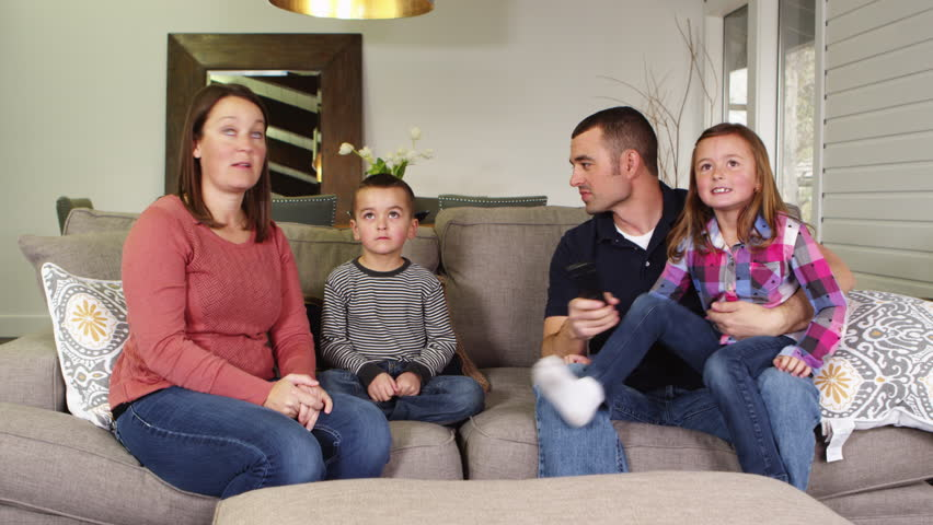family sitting on sofa watching television together with