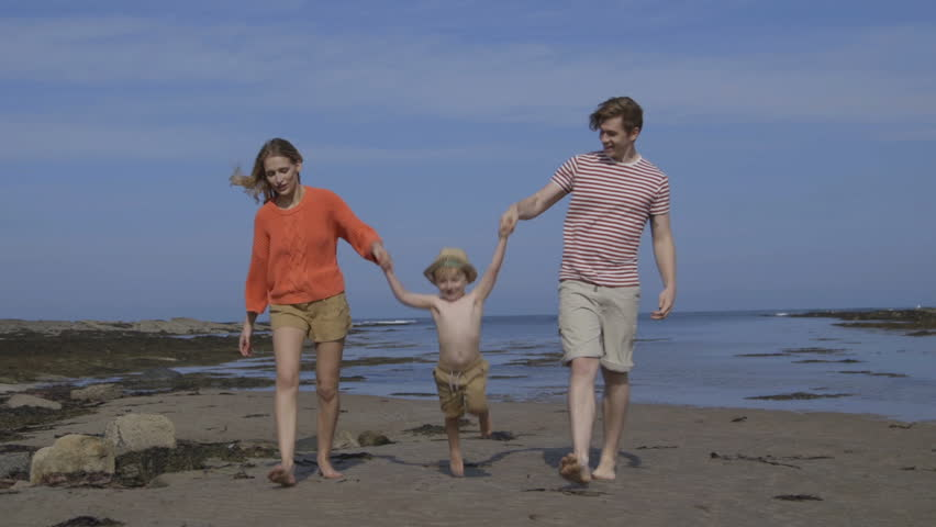 A happy little boy walks hand in hand with his parents along the beach. They are lifting him up and swinging his as they get closer to the camera. - HD stock footage clip