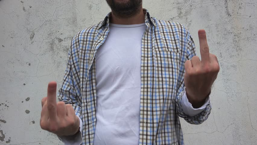 Revolting rude man gesturing middle finger as an insulting hand sign, adult male low-life on the street, youth lifestyle, unusual framing