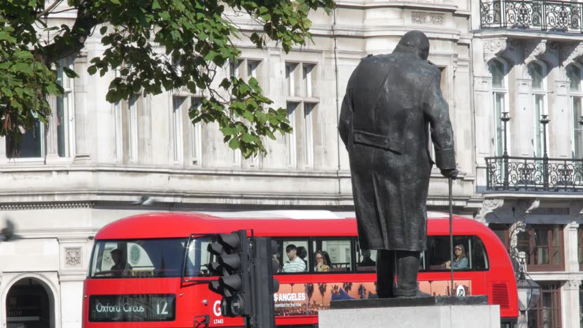 LONDON/ENGLAND - SEPTEMBER 10th 2015:New London Routemaster bus pulls away from traffic lights as Winston Churchill looks on. Shot in 4K