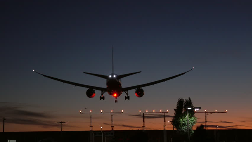 A Commercial Jet Airliner Flying Overhead Very Low Landing At Sunset In Toronto At Pearson International Airport