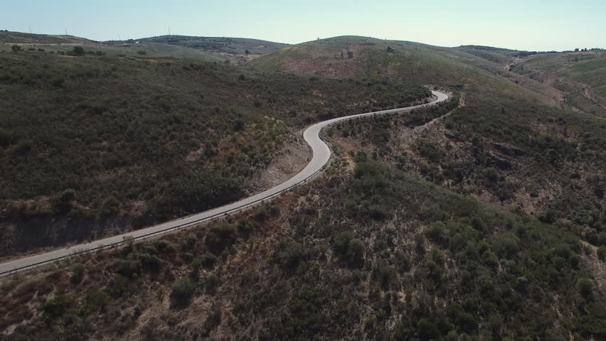 High slope mountain and cyclist climbing, aerial view, elevating camera, curved road