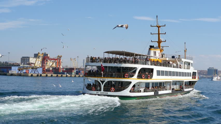 ISTANBUL - MAY 2, 2015: (Slow Motion) Flock of sea birds following the city cruise ship, sailing to Kadikoy. Ship following seagulls of Istanbul. SM