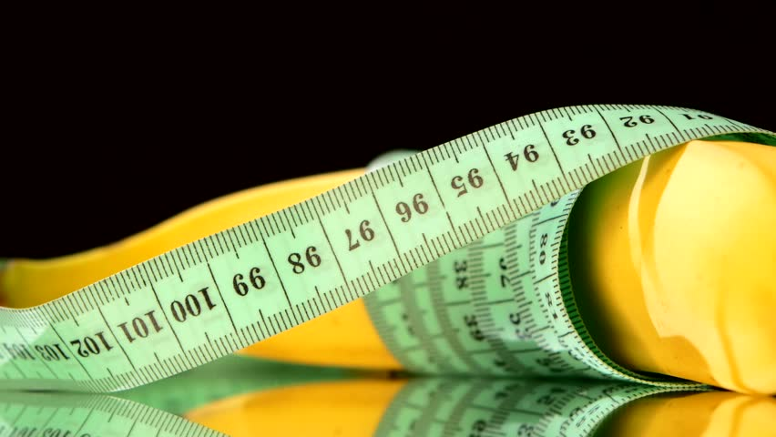 Banana wrapped up with measure tape, reflection, rotation, close up, on black background - 4K stock footage clip