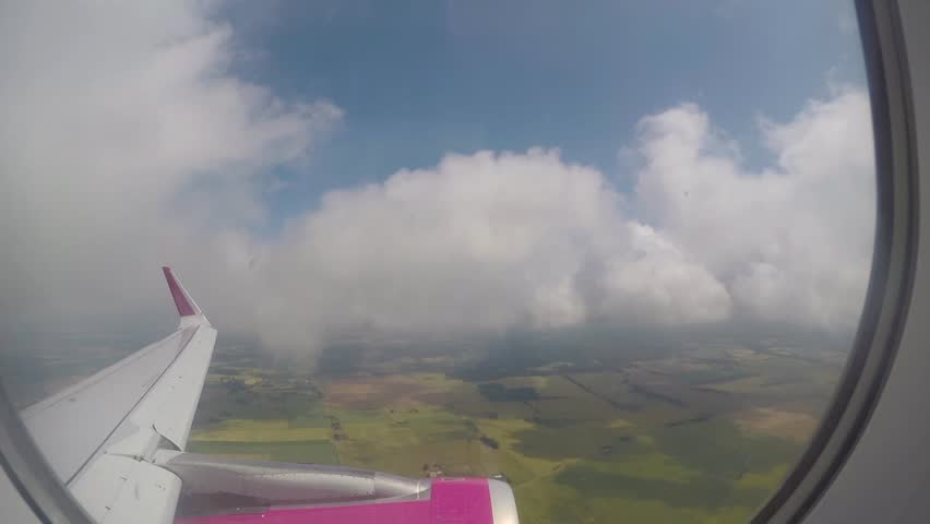 Footage of a view from airplane in flight, with airplanes wing visible, while the plane is flying through clouds. - HD stock footage clip