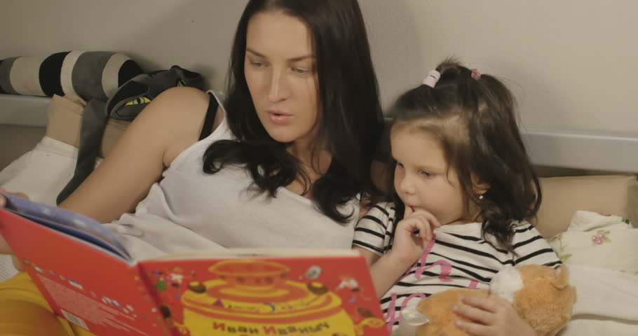 Mother, daughter reading a book before bedtime. Filmed with the Steadicam to 4K, without color correction. | Shutterstock HD Video #12624416