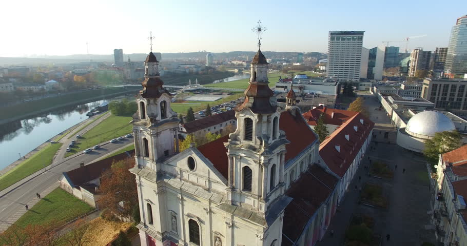 AERIAL flight around Vilnius St. Archangel Raphael Church in Lithuania. Panorama of Vilnius: Gediminas castle, Neris river, Europa, White bridge, old town and other objects