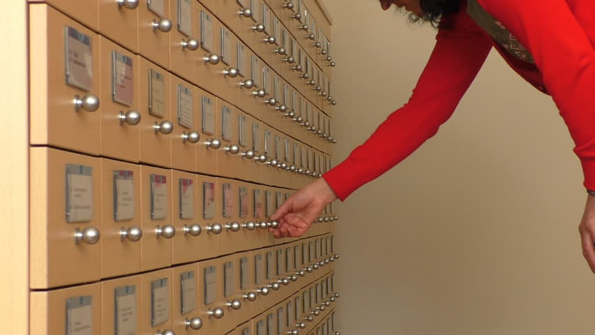 Woman in the office searching for a file by opening card index cabinet drawers