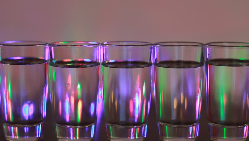 alcohol glasses with party lamps background - HD stock footage clip