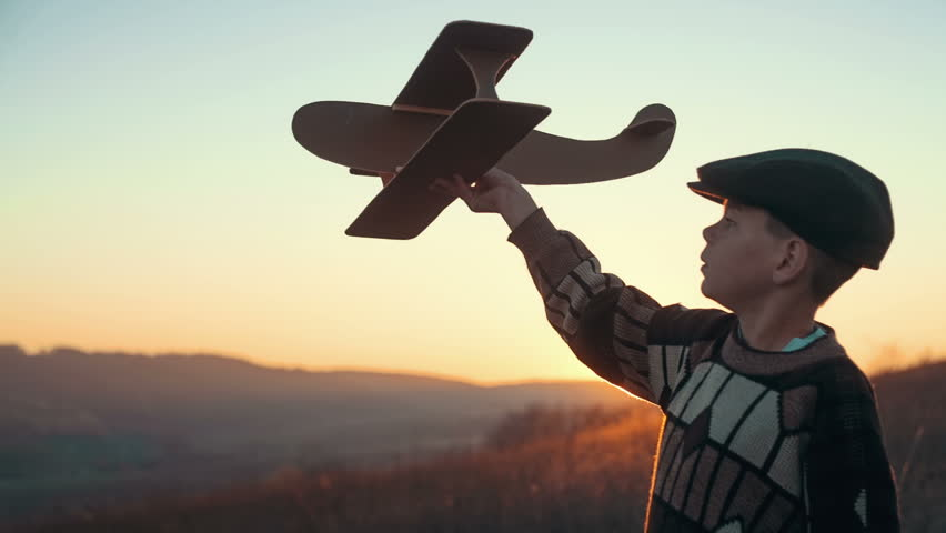 Boy playing with toy airplane against blue summer sky background and sunset