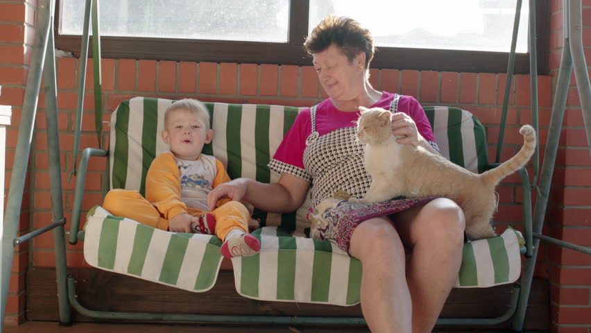 Little boy and his grandmother are sitting on the garden swing bench and talking. - HD stock video clip