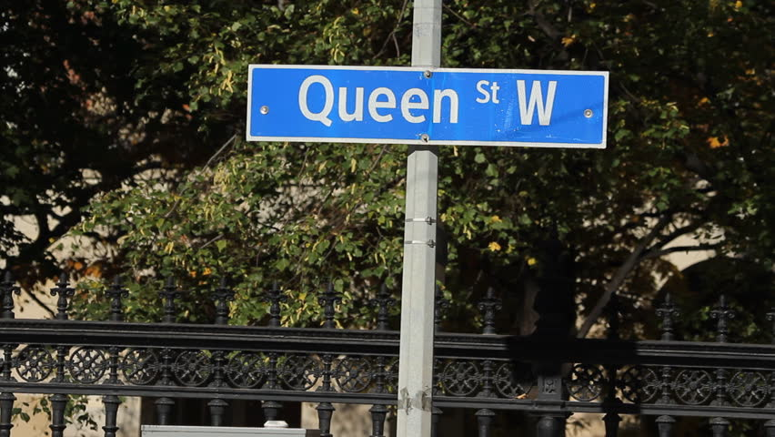 Queen Street West sign with traffic and streetcar. Toronto, Canada.