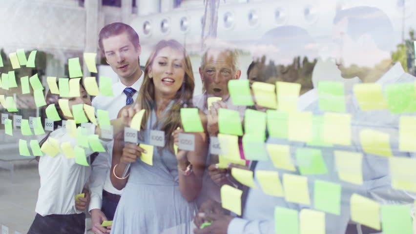 4K Attractive mixed ethnicity business team brainstorming for ideas with sticky notes in modern office. Shot on RED Epic. - 4K stock footage clip