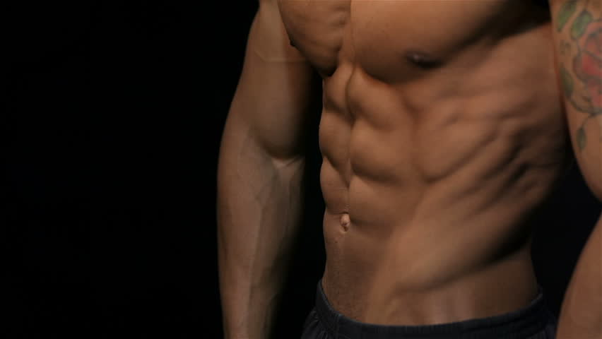 Close up man showing a perfect ABS. Muscular man bodybuilder. Man posing on a black background, shows his muscles. Bodybuilding, posing, black background, muscles - the concept of bodybuilding