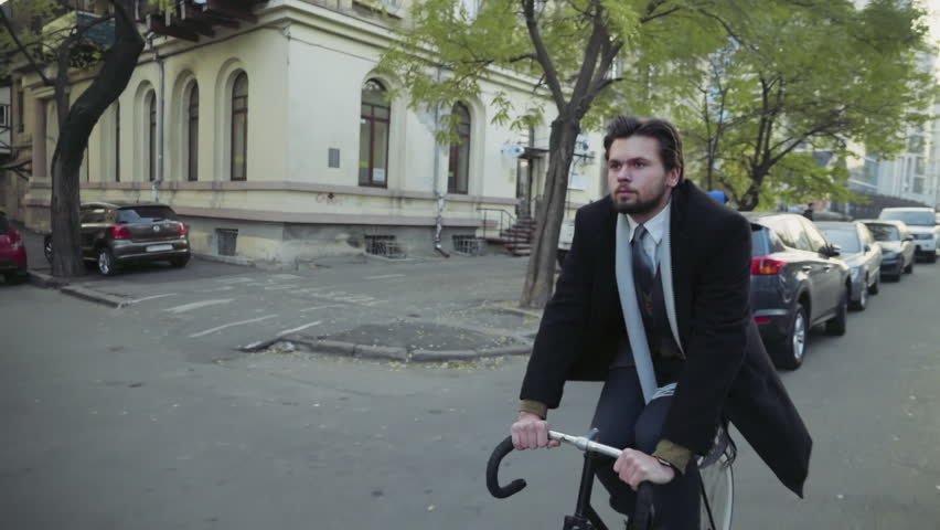handsome businessman riding a bicycle in the city street slow motion