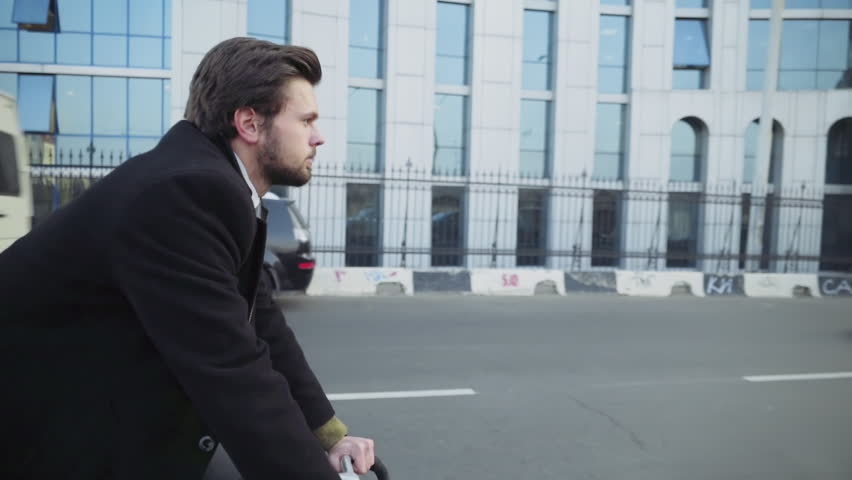 handsome businessman riding a bicycle in downtown slow motion