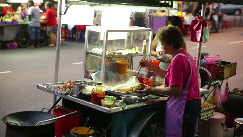 PENANG MALAYSIA CIRCA MARCH 2015,Street food cart vendor Chulia St preparing noodle dish early evening. Ingredients visible on food cart, passing cars in street, 2nd food vendor visible in distance - HD stock video clip