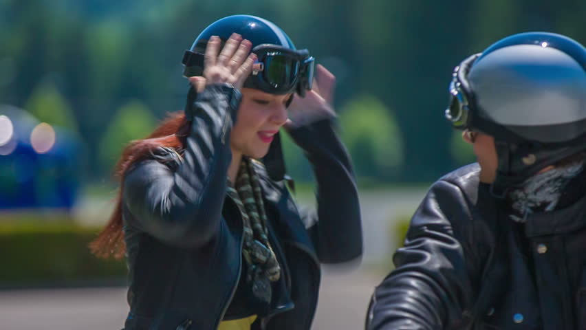 A young man driving to the corporate store and greeting his friend. She puts on her helmet and sits behind him on his motorcycle. They both drive away. The day is bright and sunny. Close-up shot - HD stock footage clip
