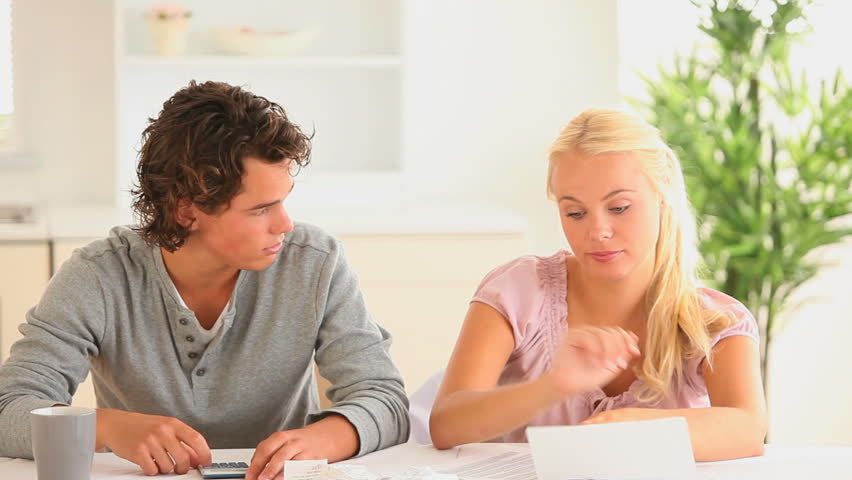 Worried couple checking at their expenses in a living room - HD stock footage clip