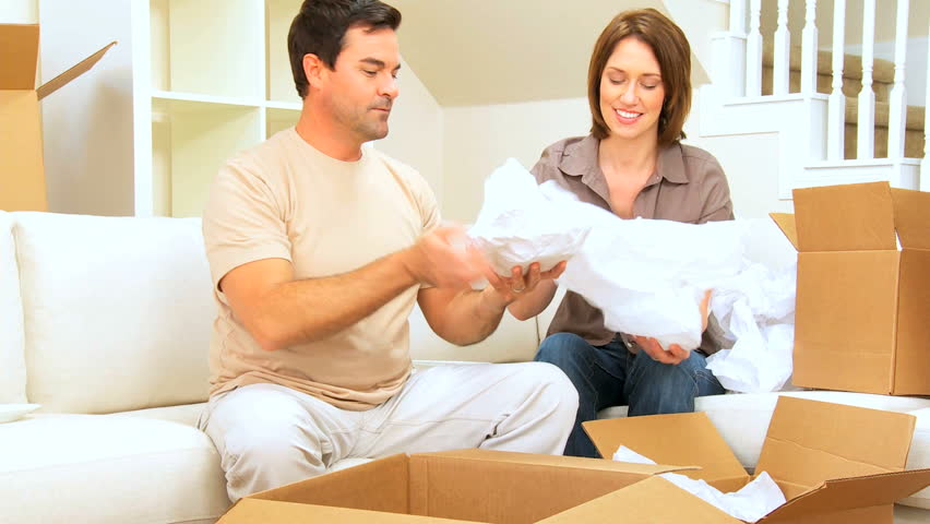 Young caucasian couple unwrapping their possessions following house move - HD stock video clip