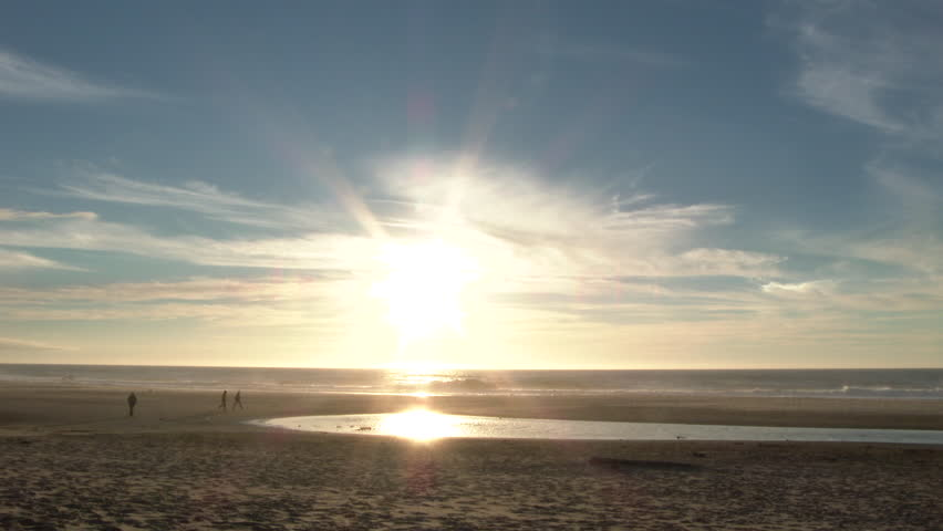 Unrecognizable people walking on wide open sandy beach in Oregon with sun setting just above the horizon.