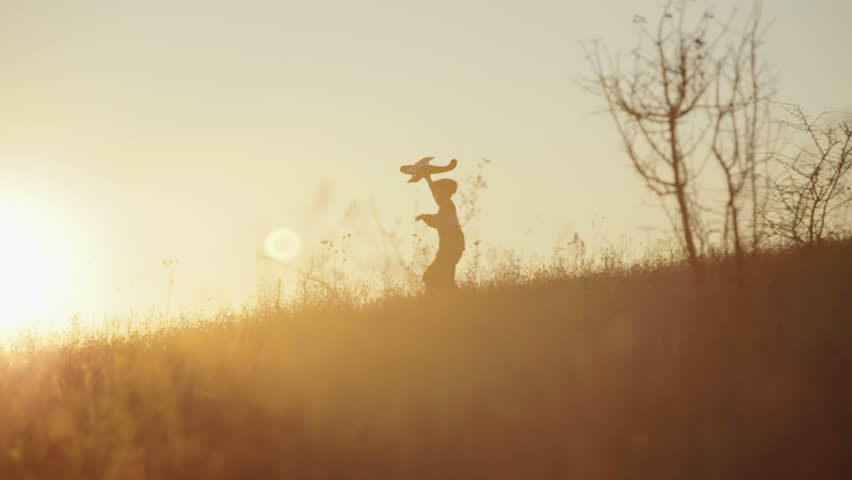 Boy with the airplane in the hands of running on a hill at sunset
