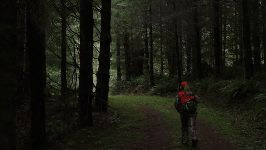 Unrecognizable woman walking away through forest in Washington State during hunting season.