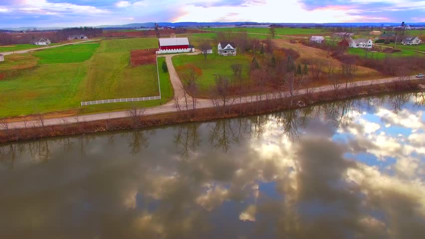 Breathtaking rural midwest landscape with morning sky reflected in calm river, aerial flyover.