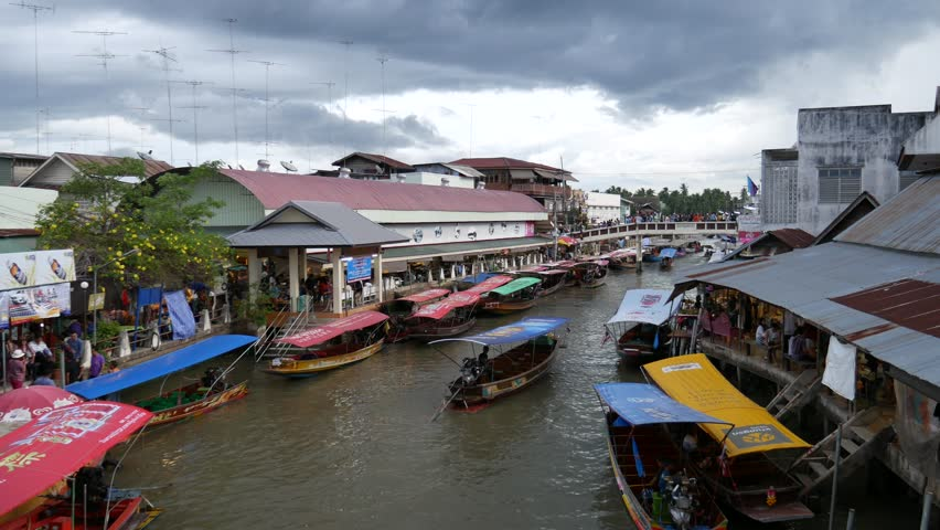 Samut Songkhram, Thailand – September 5, 2015: View of Amphawa Floating Market. People walk, shop, eat and take photos around the area. Some vendors sell food on their boats.