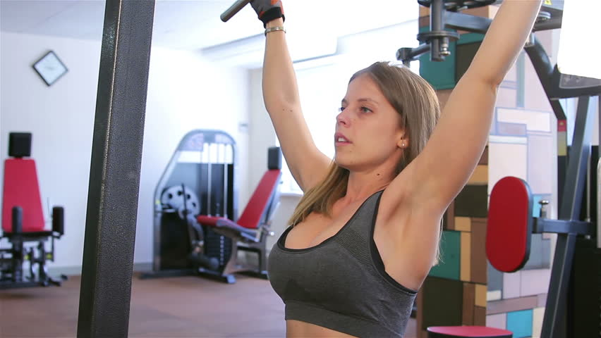 Bodyfitness workout. Athletic trainer for hands. Young woman doing exercises on athletic trainer in the gym