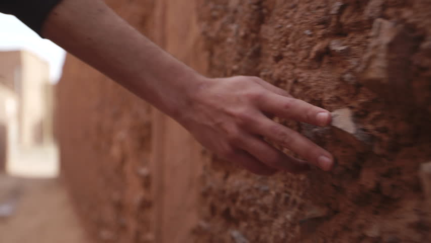 Man walks and grazes hand on stone wall. Shot in Morocco.