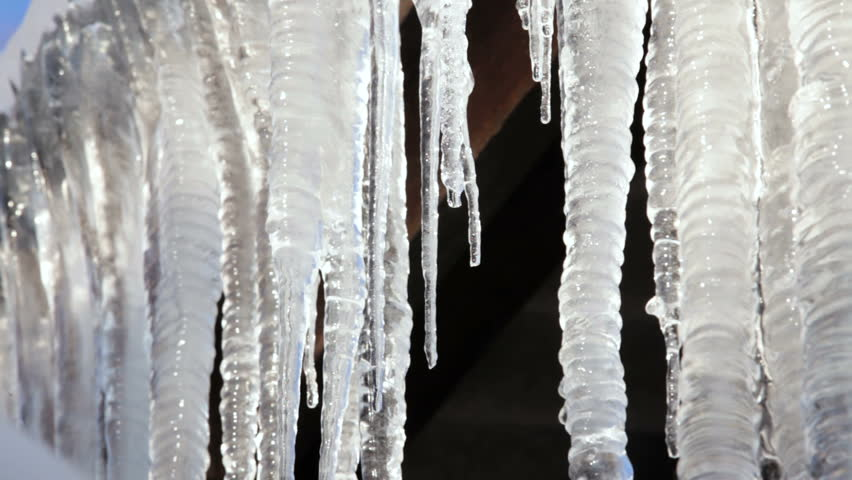 Melting Icicles Over Blue Sky Background Stock Footage