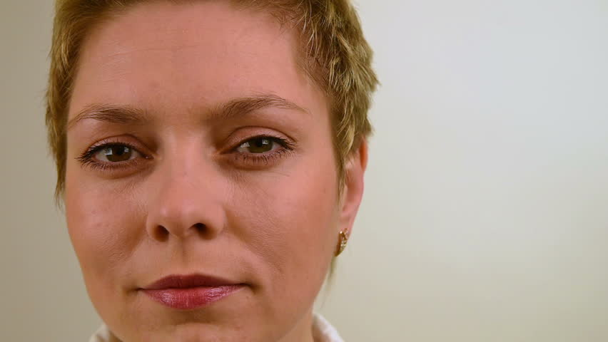 Pretty short hair blond girl looks at the camera straight. Face close up over white background - HD stock footage clip