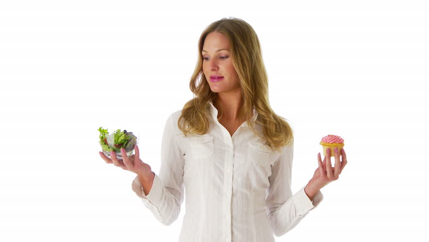 Woman deciding between salad and cupcake - HD stock footage clip