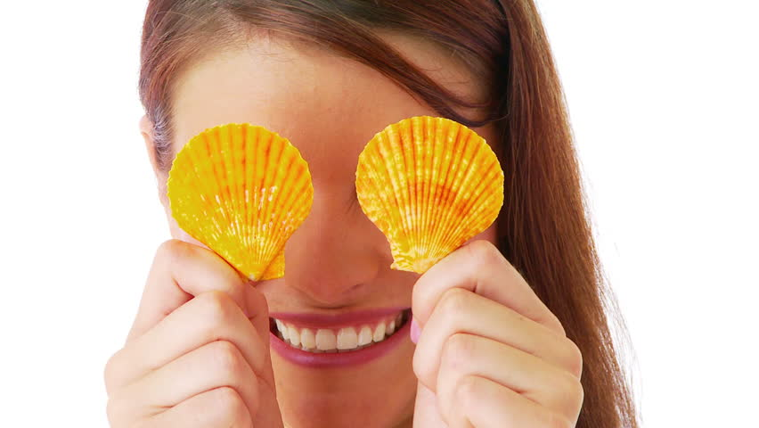 Woman playing peekaboo with sea shells - HD stock footage clip