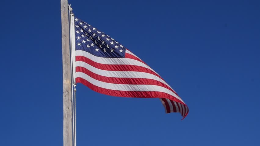 A slow motion shot of a beautiful American flag blows in a strong wind against a blue sky backdrop - HD stock footage clip